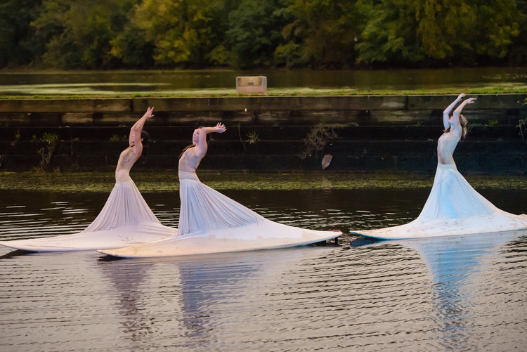Performers in elegant dresses dancing on boats.