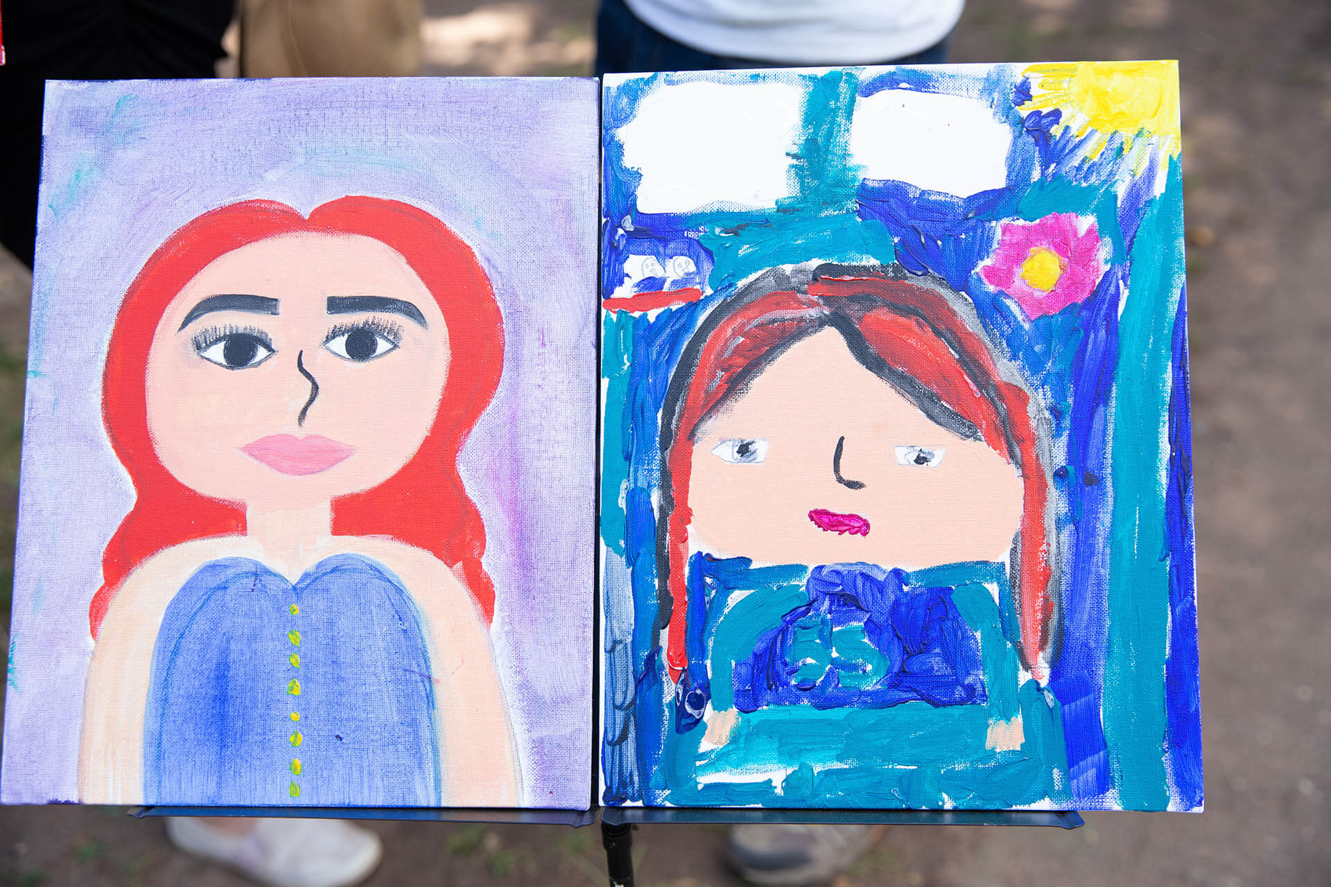 Children showing paintings they made at an art show.