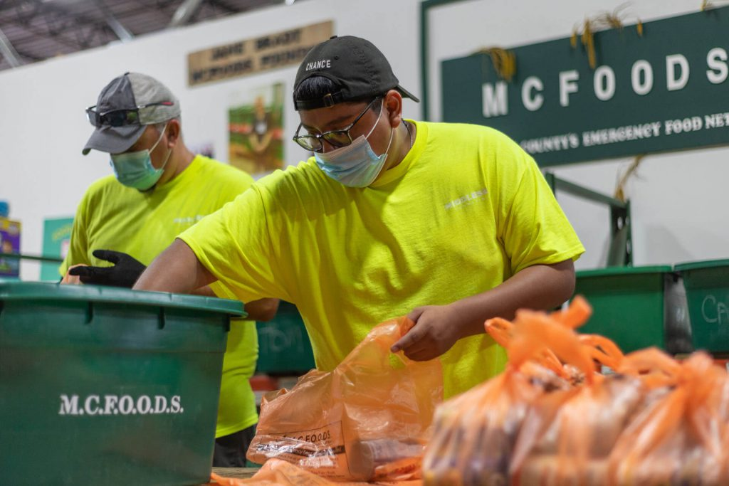 A volunteer works at MCFOODS, a local food pantry, to package meals for those in need.